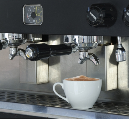 Coffee cup filled with cappuccino coffee, sitting on the tray of a commercial espresso machine Imagens