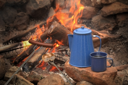 percolator: hotdog and marshmallows roasting over a campfire next to a blue enamel coffee pot and mug filled with coffee Stock Photo