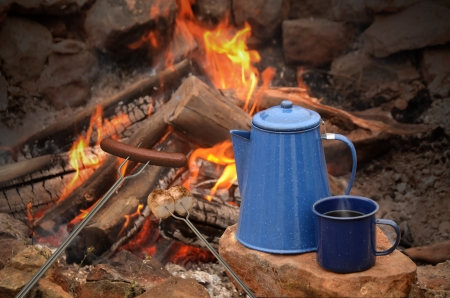 camp fire: hot dog on a long fork over a fire next to an enamel coffee percolator and mug full of coffee  Stock Photo