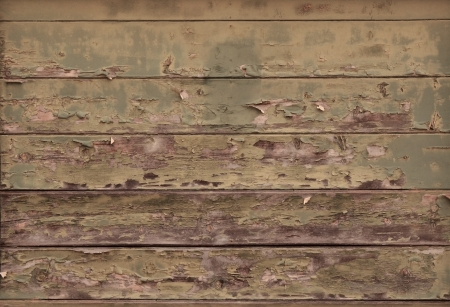 distressed: Distressed wood planks on an aged building showing blistered paint and wood grain Stock Photo