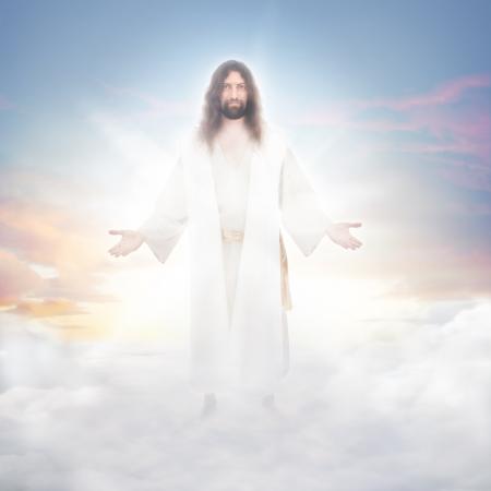 Jezus verrezen in de hemelse wolken gebaad in lichtgevend licht Stockfoto