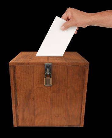A mans hand putting an envelope in the slot of a box photo