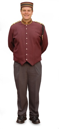 bellhop: Bellhop standing with his hands behind his back, smiling at the camera, on a white background. Stock Photo