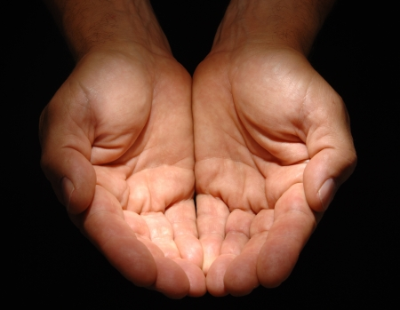 begging: Close up of a mans cupped hands under a spotlight on a black background.