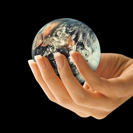 cradling: Side view of a womans hand holding the earth on a black background.