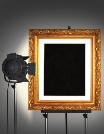Empty gold frame being lit by a spotlight sitting on an easel.