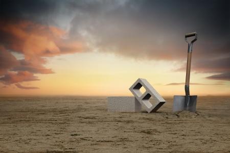 amanecer: Imagen de dos bloques de cemento de cenizas en la arena al lado de una pala al atardecer. Foto de archivo