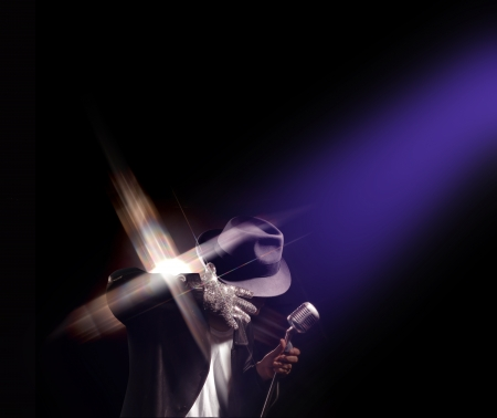 Spotlight shining down on a Michael Jackson impersonator performing.