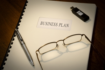 Business Plan on a desk wiht a pen, a thumb drive and a pair of glasses Stock Photo