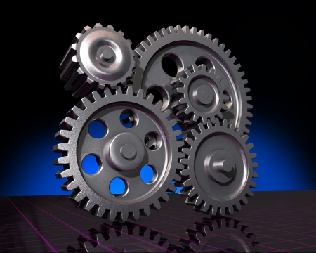 Five machine gears on a reflective surface and a dark background