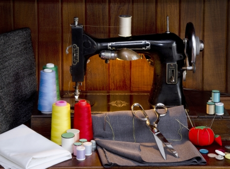Retro sewing machine with sewing paraphernalia including thread, fabric, sewing needles, pin cushion, buttons scissors and thimble