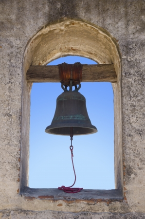 A photo of a mission bell on a historical missionary building