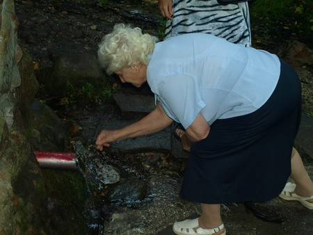 Old woman drinks clear and health-giving water from the spring in the shrine of the Holy Otylia in Urzedow, Poland