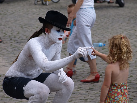 Street actor play with young girl (tourist) on Old Market Place in Kazimierz Dolny, Poland