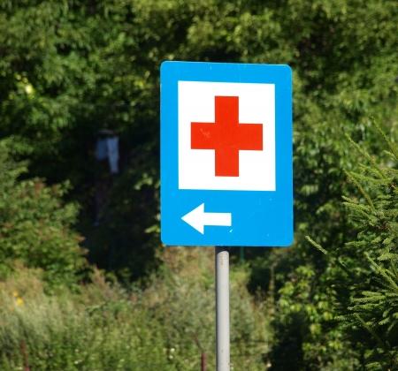 rood kruis: Kazimierz Dolny, Polen - 27 juli 2008 - Ziekenhuis bord met rood kruis en de pijl op straat