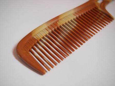 plastic comb: single brown comb at the white background