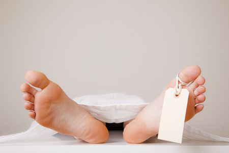 symbol victim: Two feet of a dead body, with an identification tag - blank sign attached to a toe. Covered with a white sheet. Stock Photo