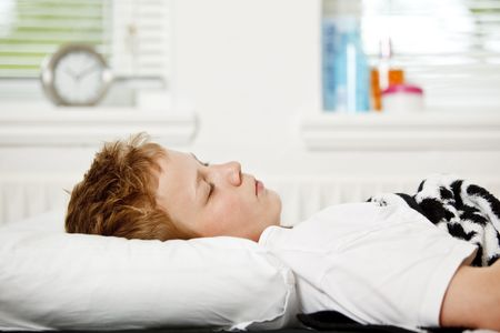 Boy sleeping on his back in bed Stock Photo - 6035380