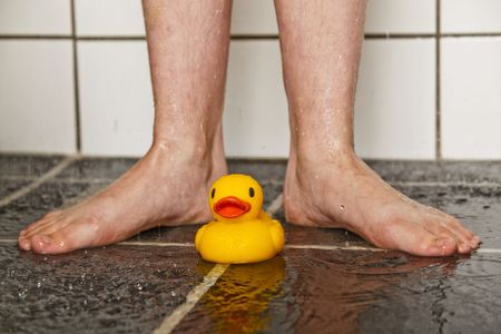 Feet of boy in shower with a lonely rubber duck