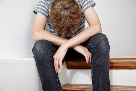 personas tristes: Chico de aspecto triste molest� despu�s de problemas dom�sticos. Sentado en la escalera de ocultar su rostro y llorando.  Foto de archivo