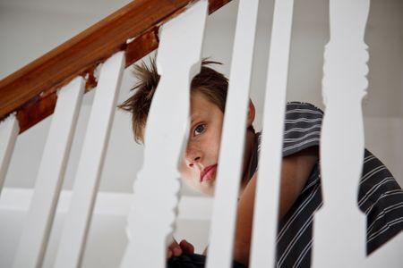 国内トラブル後悲しい男の子を混乱させます。手すりを探して階段に座っています。 写真素材