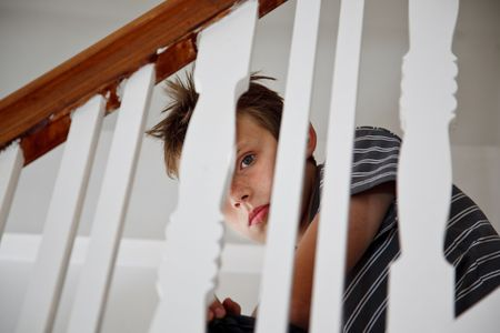 Sad looking boy upset after domestic trouble. Sitting on the staircase looking through the handrail.