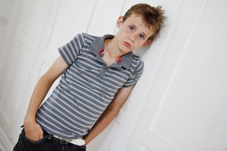 Sad looking boy upset after domestic trouble. Leaning against white wall. Stock Photo - 6035471