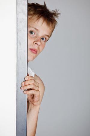 Boy looking through the doorway photo