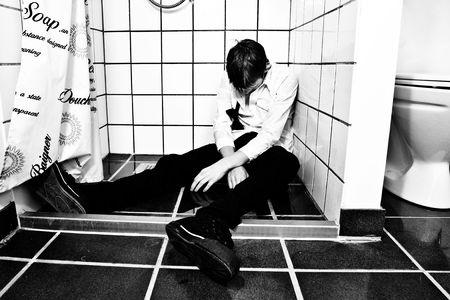 jovenes tomando alcohol: Vestidos para fiesta, remojo h�medo y el inconsciente en la ducha  Foto de archivo