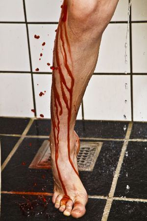 Leg with blood and water running down onto the floor of the shower. Stock Photo - 6035455