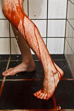 Legs with blood and water running down onto the floor of the shower.