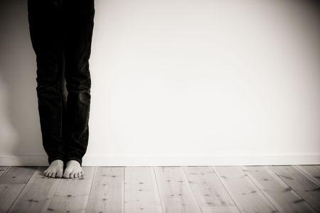 ojos tristes: Las piernas y los pies descalzos de muchacho recostada contra la pared  Foto de archivo
