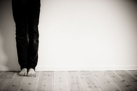 boy alone: Legs and bare feet of boy leaning against wall