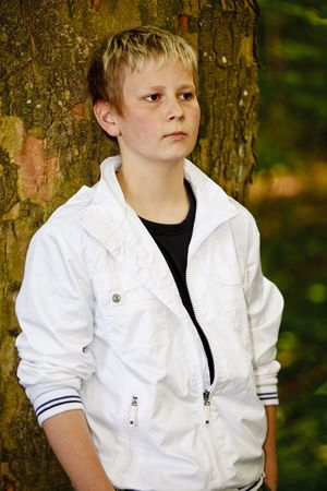 Boy leaning against a tree in the park photo