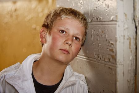 Young boy leaning against old door
