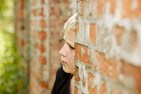 古い家のレンガの壁にもたれて悲しい探している少年