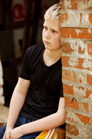 Sad looking boy leaning against brick wall of an old house
