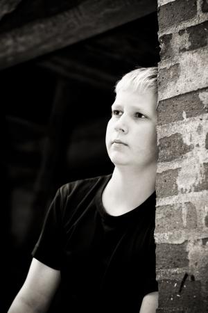 bambini pensierosi: Triste ragazzo cercando pendente contro un muro di mattoni di una vecchia casa