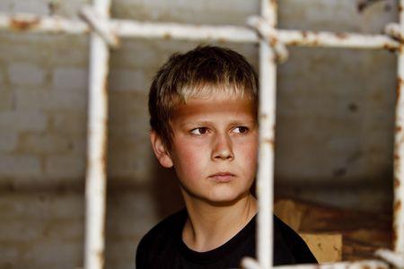 Portrait of young boy looking through bars in the window Standard-Bild