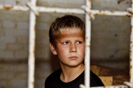 Portrait of young boy looking through bars in the window Imagens