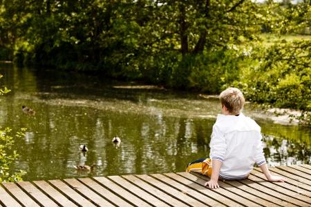 Young boy sitting on a bridge looking at the stream below Standard-Bild