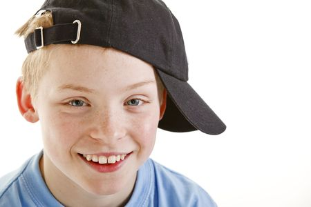 boy 12 year old: Portrait of happy smiling 12 year old boy with a cap isolated on white background Stock Photo