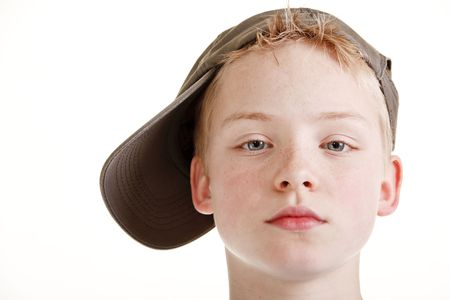 Portrait of young boy with a serious looking face and wearing a cap
