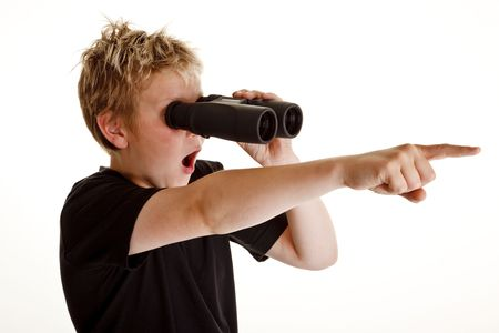 Teenage boy looking through binoculars and pointing with his finger Stock fotó