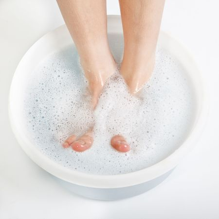 Feet of boy in foot bath Imagens