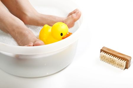 Boy having a foot bath with rubber duck floating in the tub