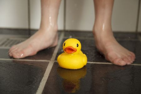 Rubberduck in front of feet of boy in shower