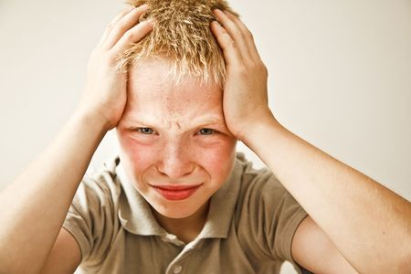 Portrait of young boy in pain from headache