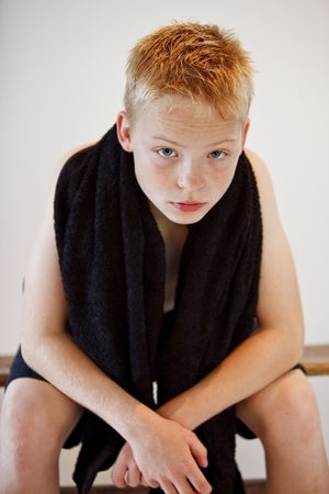Young boy sitting on a bench with a towel around his neck