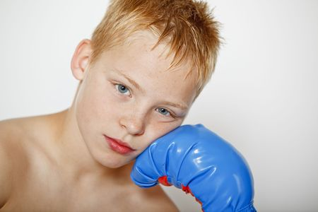 Closeup portrait of a young boy wearing boxing gloves photo